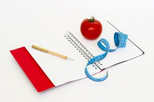 Notebook, tomato and measuring tape